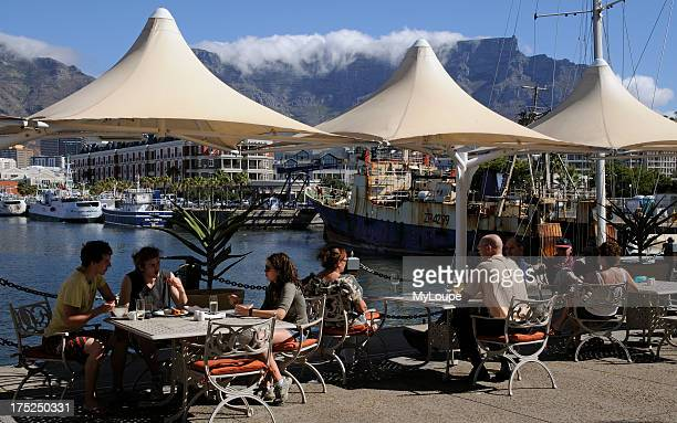 Customers eating and drinking at the VA waterfront and harbour Cape Town South Africa