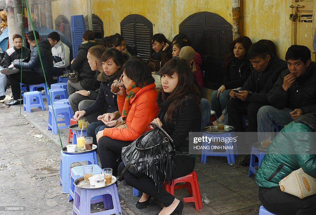 Customers enjoy coffee at a coffee shop set up on a sidewalk in the ancient quarter of Hanoi on January 3, 2013. Starbucks said on January 3 it would open its first store next month in Vietnam, seeking a foothold in the coffee-loving country as part of efforts to expand in Asia. AFP PHOTO / HOANG DINH Nam