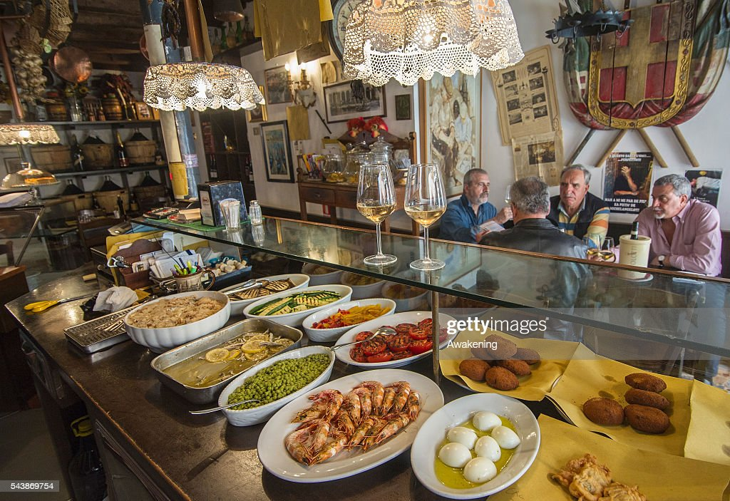 Customers enjoy drinks at 'Osteria da Alberto' bacaro on June 30, 2016 in Venice, Italy. The bacari which opens for lunch and dinner are the local down to earth version of a wine bars. Venetians stop to snack and enjoy 'ciccheti, a kind of Tapas traditionally washed down with a glass of wine.