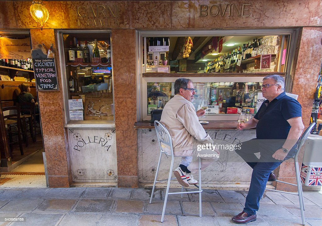 Customers enjoy drinks at 'Un Mondo Divino' bacaro on June 30, 2016 in Venice, Italy. The bacari which opens for lunch and dinner are the local down to earth version of a wine bars. Venetians stop to snack and enjoy 'ciccheti, a kind of Tapas traditionally washed down with a glass of wine.