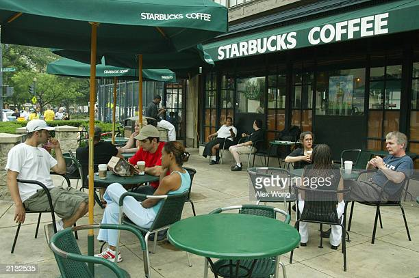 Customers enjoy their beverages July 2 2003 outside a Starbucks coffee shop at Dupont Circle in Washington DC Starbucks' stocks advanced $167 to $27...
