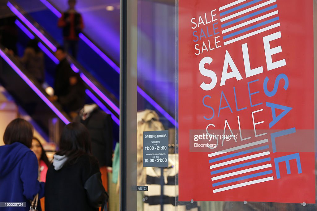 Customers enter a clothing store as a sale sign is displayed in the Ginza district of Tokyo, Japan, on Friday, Jan. 25, 2013. Japan's consumer prices fell for the seventh time in eight months, underscoring the risk that the central bank may struggle to reach a 2 percent inflation target unless it implements new easing measures earlier than planned. Photographer: Kiyoshi Ota/Bloomberg via Getty Images