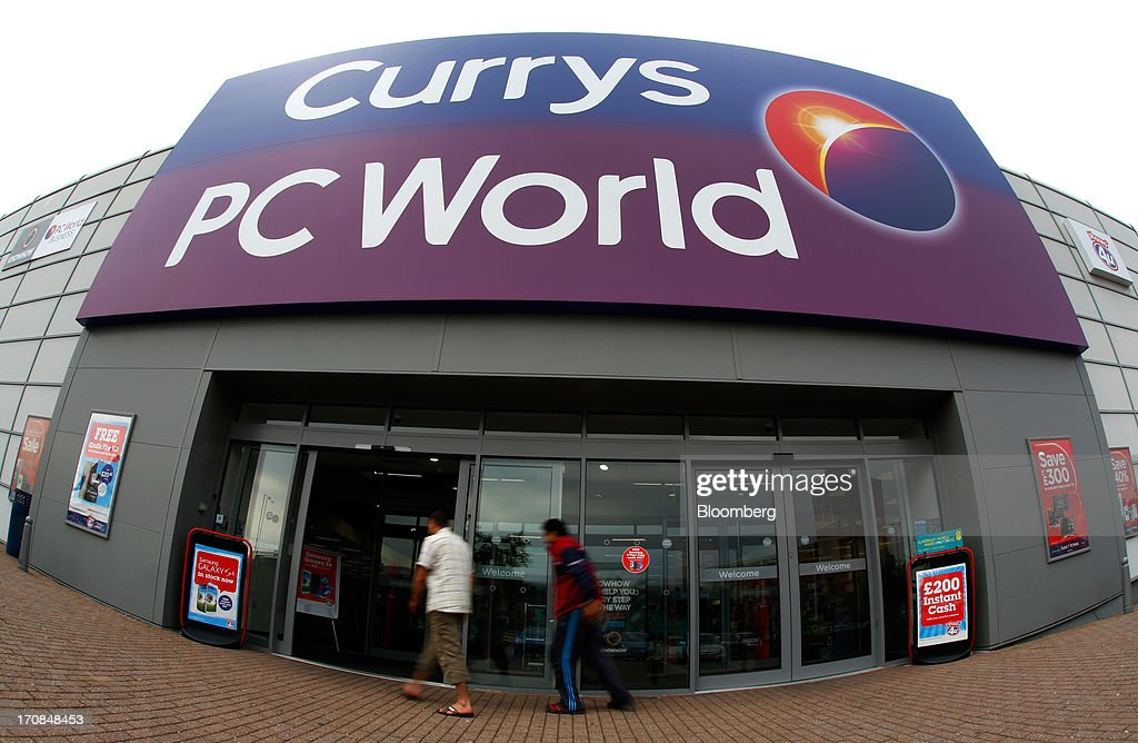Customers enter a Currys and PC World 2 in 1 store, operated by Dixons Retail Plc, in Manchester, U.K., on Tuesday, June 18, 2013. Dixons Retail Plc, the U.K.'s largest consumer-electronics retailer, said last month it will report annual pretax profit at the 'top end' of analysts' predictions after fourth-quarter revenue beat estimates on increased sales of tablets and services such as software tutorials. Photographer: Paul Thomas/Bloomberg via Getty Images