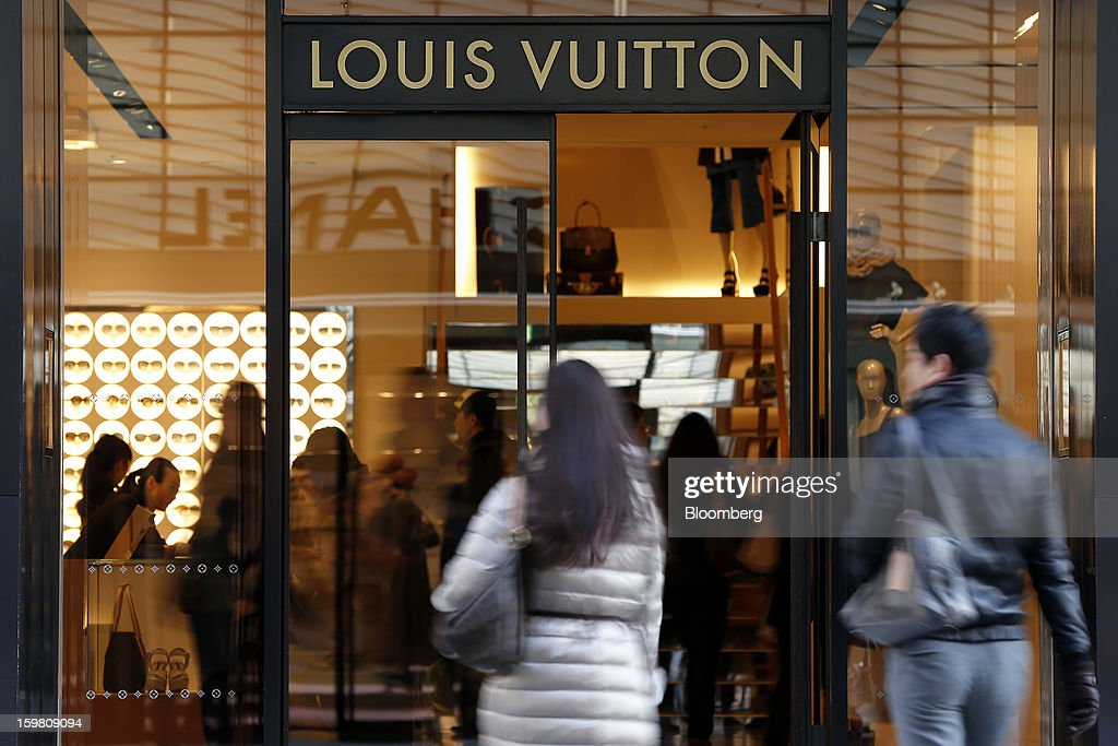 Customers enter a Louis Vuitton store, operated by LVMH Moet Hennessy Louis Vuitton SA, in the Ginza district of Tokyo, Japan, on Sunday, Jan. 20, 2013. Japan's consumer prices excluding fresh food, a benchmark monitored by the central bank, haven't advanced 2 percent for any year since 1997, when a national sales tax was increased. Photographer: Kiyoshi Ota/Bloomberg via Getty Images