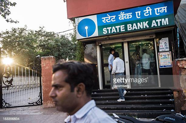 Customers enter a State Bank of India automated teller machine branch in Jaipur Rajasthan India on Wednesday Oct 3 2012 The Indian economy will...
