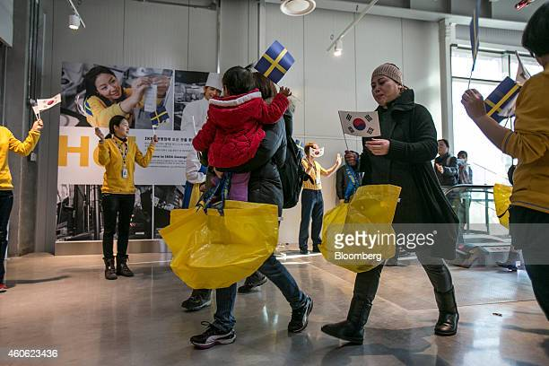 Customers enter an Ikea AB store carrying shopping bags during the opening of the company's store in Gwangmyeong Gyeonggi province South Korea on...