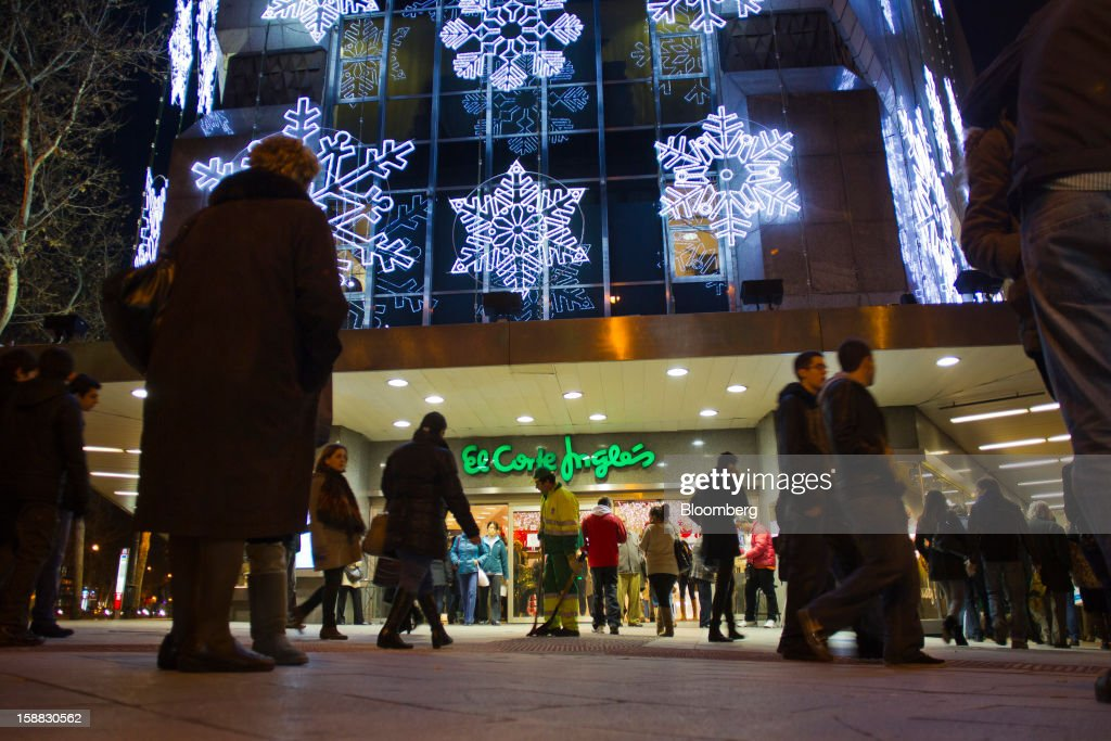 Customers enter and exit the El Corte Ingles SA department store in central Madrid, Spain, on Saturday, Dec. 29, 2012. Spain's economic activity kept falling in the fourth quarter, Bank of Spain says. Photographer: Angel Navarrete/Bloomberg via Getty Images
