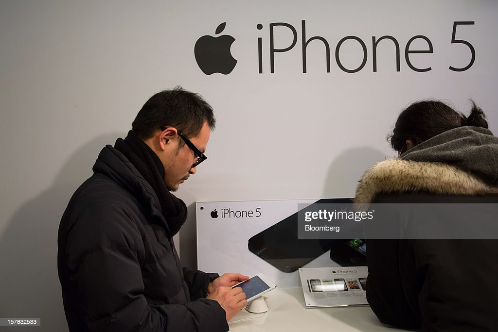 Customers examine an Apple Inc. iPad Mini, left, and iPhone 5 during a launch event organized by SK Telecom Co. in Seoul, South Korea, on Thursday, Dec. 6, 2012. The iPhone 5 went on sale in South Korea today. Photographer: SeongJoon Cho/Bloomberg via Getty Images