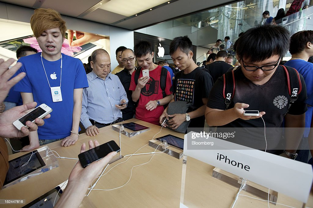 Customers examine Apple Inc. iPhone 5 smartphones at the company's store in Hong Kong, China, on Friday, Sept. 21, 2012. Apple is poised for a record iPhone 5 debut and may not be able to keep up with demand as customers line up from Sydney to New York to pick up the latest model of its top-selling product. The device hits stores in eight countries today at 8 a.m. local time, giving customers in Australia the first chance to buy the device. Photographer: Daniel J. Groshong/Bloomberg via Getty Images