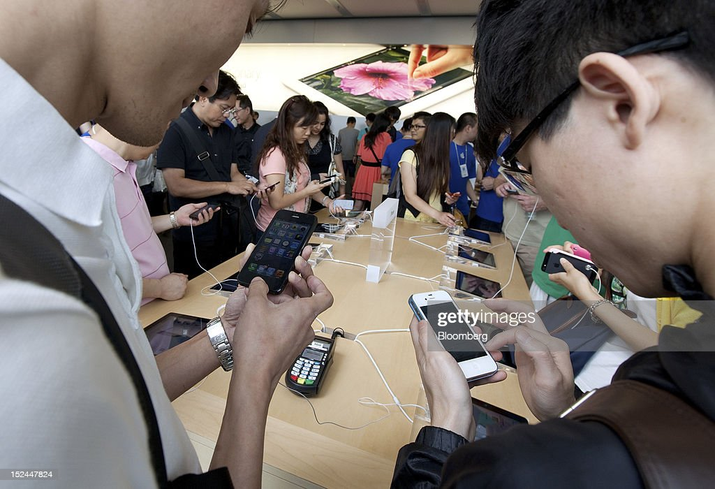 Customers examine Apple Inc. iPhone 5 smartphones at the company's store in Hong Kong, China, on Friday, Sept. 21, 2012. Apple Inc. is poised for a record iPhone 5 debut and may not be able to keep up with demand as customers line up from Sydney to New York to pick up the latest model of its top-selling product. The device hits stores in eight countries today at 8 a.m. local time, giving customers in Australia the first chance to buy the device. Photographer: Daniel J. Groshong/Bloomberg via Getty Images
