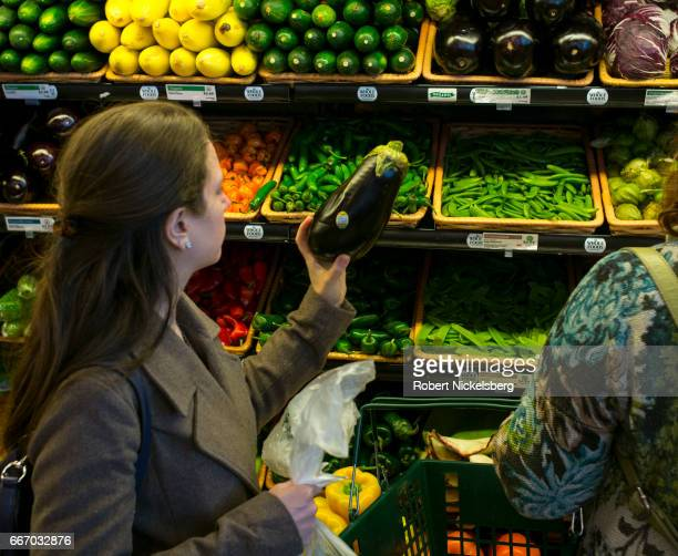 Customers examine fresh vegetables April 9 2017 at the Whole Foods Market in Darien Connecticut Whole Foods Market was started in 1980 in Austin...