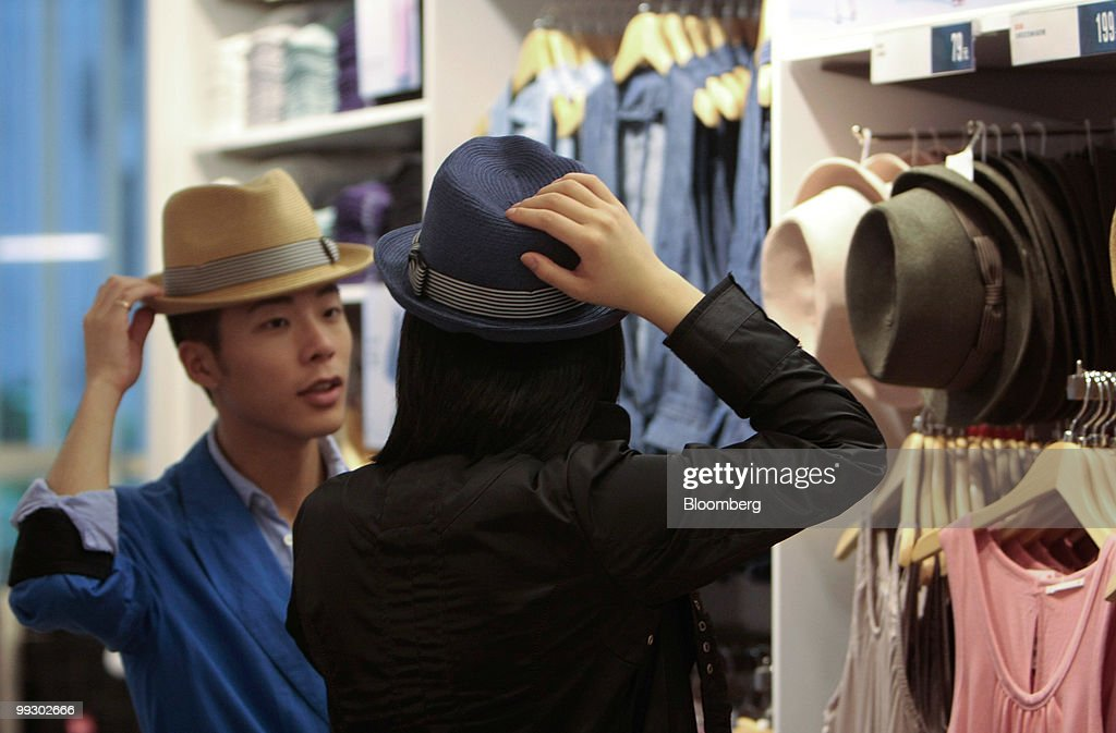 Customers examine hats at the Uniqlo store owned by Fast Retailing Co in Shanghai China on Friday May 14 2010 Fast Retailing Co plans to increase the...