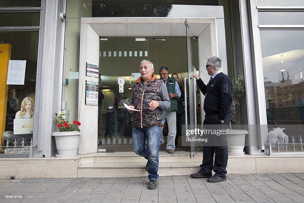Customers exit a Bank of Cyprus Plc branch as banks open for the first time in two weeks in Nicosia, Cyprus, on Thursday, March 28, 2013. The Central Bank of Cyprus's capital controls will include a 300-euro ($383) daily limit on withdrawals and restrictions on transfers to accounts outside the country. Photographer: Simon Dawson/Bloomberg via Getty Images