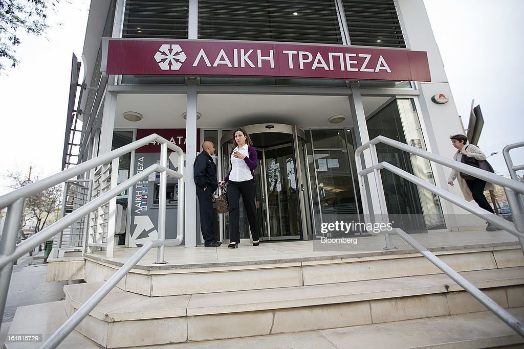 Customers exit a branch of Cyprus Popular Bank Pcl, also known as Laiki Bank as banks open for the first time in two weeks in Nicosia, Cyprus, on Thursday, March 28, 2013. The Central Bank of Cyprus's capital controls will include a 300-euro ($383) daily limit on withdrawals and restrictions on transfers to accounts outside the country. Photographer: Simon Dawson/Bloomberg via Getty Images
