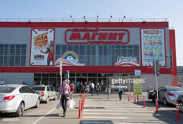 Customers exit and enter an OAO Magnit hypermarket in Krasnodar Russia on Thursday Aug 7 2014 Russia slapped import bans on an array of food goods...