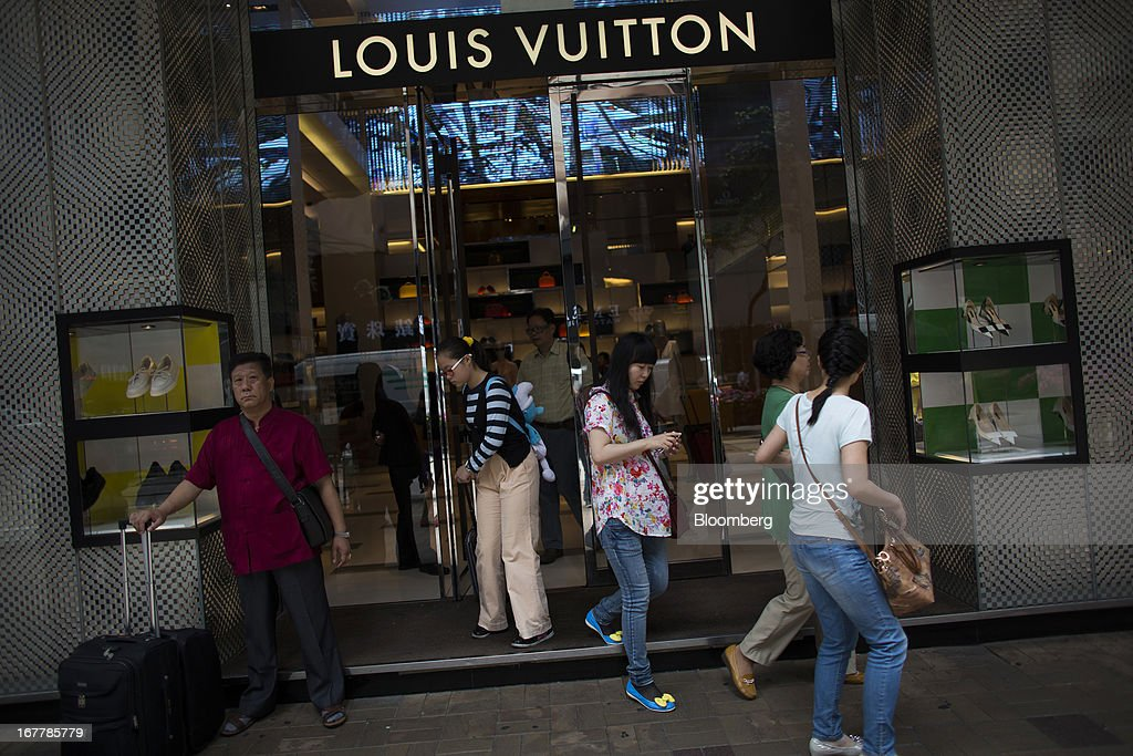 Customers exit from a Louis Vuitton store, operated by LVMH Moet Hennessy Louis Vuitton SA, in the Tsim Sha Tsui area of Hong Kong, China, on Tuesday, April 30, 2013. Financial Secretary John Tsang on Feb. 27 projected annual growth of 1.5 percent to 3.5 percent this year following 2012's 1.4 percent, the weakest rate since 2009 as Europe's sovereign debt crisis sapped global demand. Photographer: Lam Yik Fei/Bloomberg via Getty Images