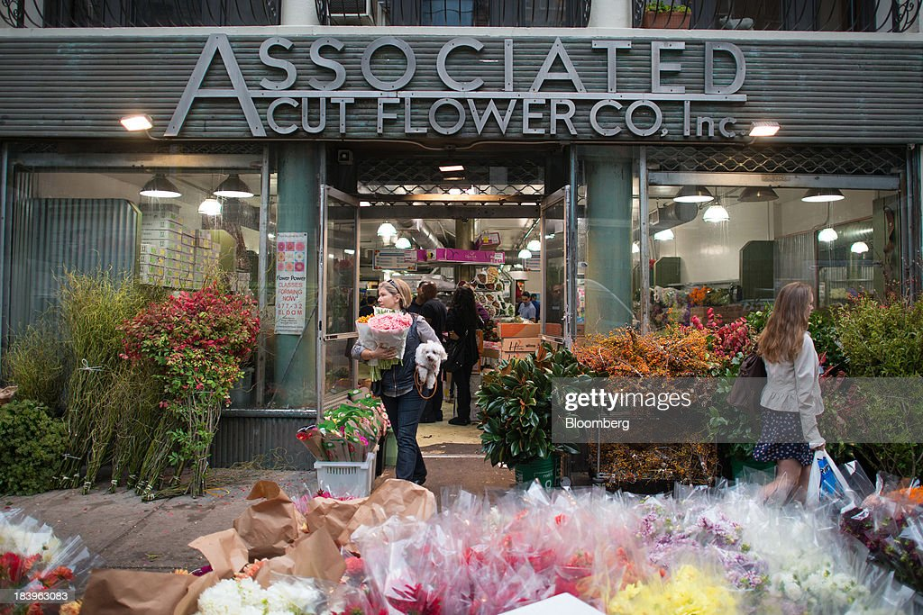 Customers exit the Associated Cut Flower Co. wholesale flower shop in New York, U.S., on Monday, Oct. 7, 2013. Wholesale inventories figures, which were scheduled for Oct. 9 by the U.S. Census Bureau, will not be released due to the partial government shutdown. Photographer: Craig Warga/Bloomberg via Getty Images