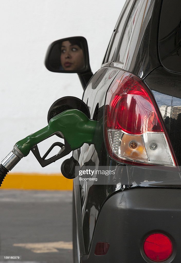 A customer's face is reflected in a side mirror as she waits for her tank to be filled with gasoline at a Pemex station in Mexico City, Mexico, on Tuesday, Jan. 8, 2013. Mexico's government is speeding up the removal of subsidies on gasoline and increasing local unleaded gasoline prices by 11 centavos in January, according to the Finance Ministry. Photographer: Susana Gonzalez/Bloomberg via Getty Images