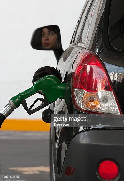 A customer's face is reflected in a side mirror as she waits for her tank to be filled with gasoline at a Pemex station in Mexico City Mexico on...
