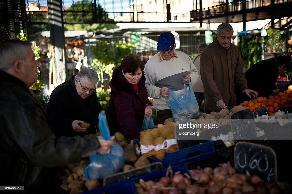 Customers fill bags with potatoes selected from a fruit and vegetable stall in the weekly market in Figueres, Spain, on Thursday, Jan. 31, 2013. Spain's recession deepened more than economists forecast in the fourth quarter as the government's struggle to rein in the euro region's second-largest budget deficit weighed on domestic demand. Photographer: David Ramos/Bloomberg via Getty Images