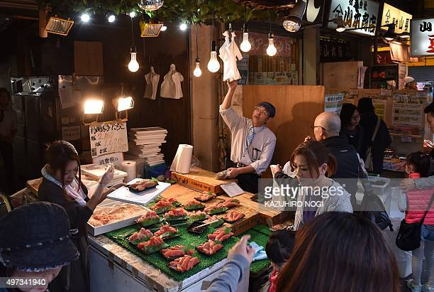 Customers gather around a seafood shop near the Tsukiji Fish Market in Tokyo on November 16 2015 Japan's economy slipped into recession for the...