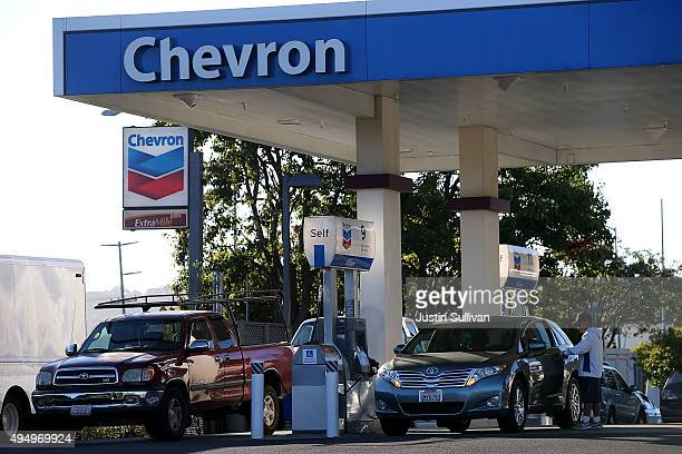 Customers get gasoline at a Chevron station on October 30 2015 in Corte Madera California Chevron announced plans to cut up to 7000 jobs as oil...