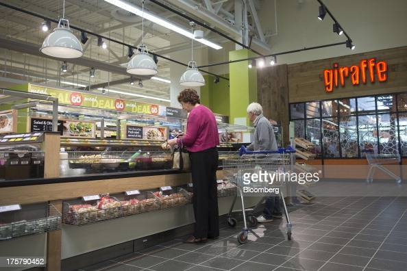 Customers help themselves to food at a selfservice counter outside a Giraffe restaurant inside a Tesco Plc store in Watford UK on Thursday Aug 8 2013...