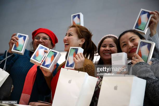 Customers hold up the new iPhone X at an Apple Store on November 3 2017 in Palo Alto California The highly anticipated iPhone X went on sale around...