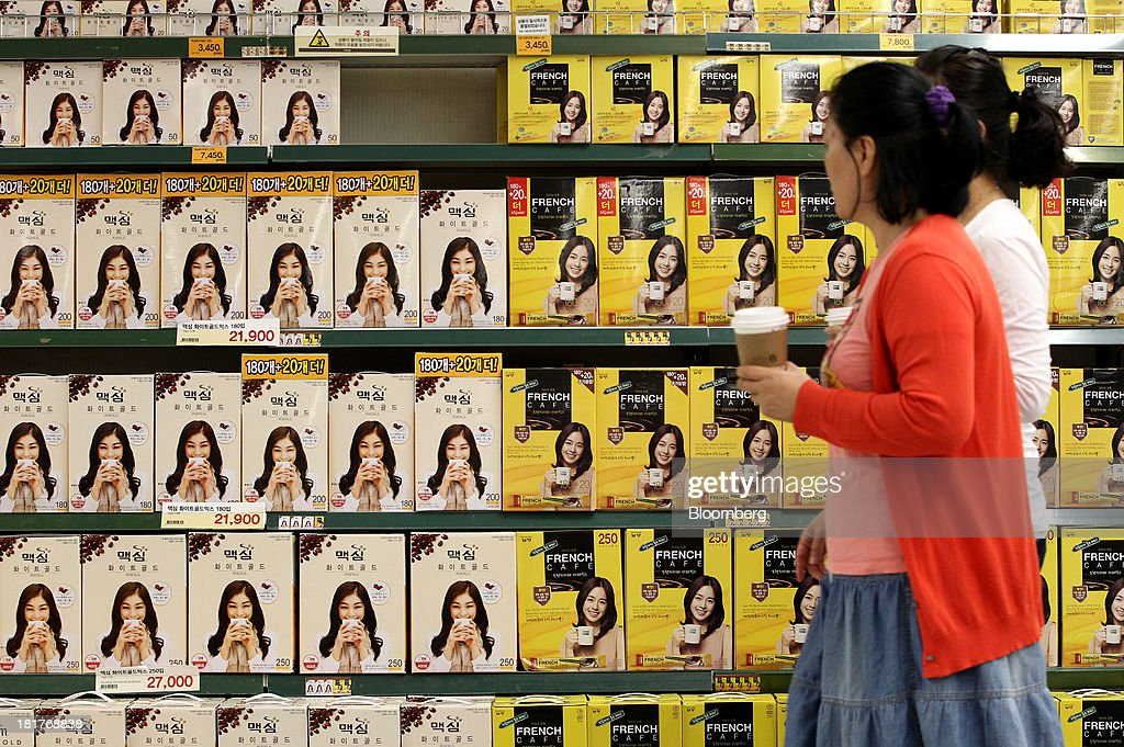 Customers holding paper cups walk past packages of coffee displayed at an E-Mart Co. store, a subsidiary of Shinsegae Co., in Seoul, South Korea, on Tuesday, Sept. 24, 2013. The South Korean economy faces headwinds, with record household debt and a sluggish housing market weighing on consumption. Photographer: SeongJoon Cho/Bloomberg via Getty Images