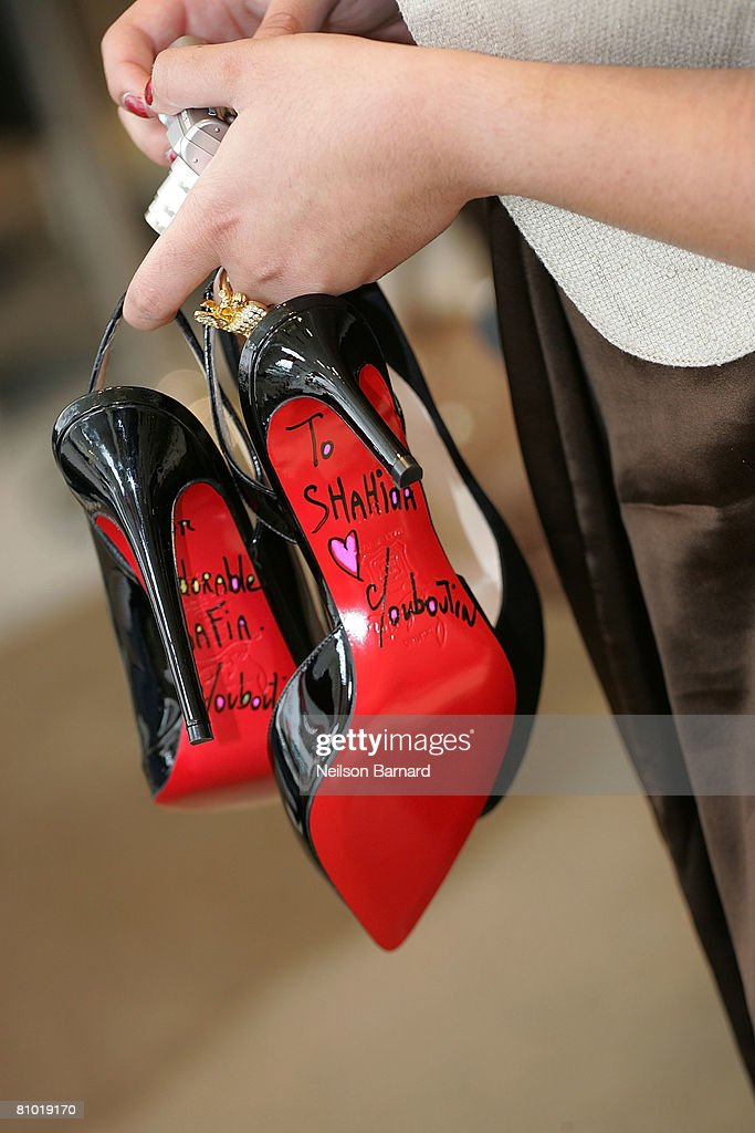 A customers holds her newly autographed Christian Louboutin shoes at the launch of his new fall collection at Barneys New York on May 7, 2008 in Beverly Hills, California.