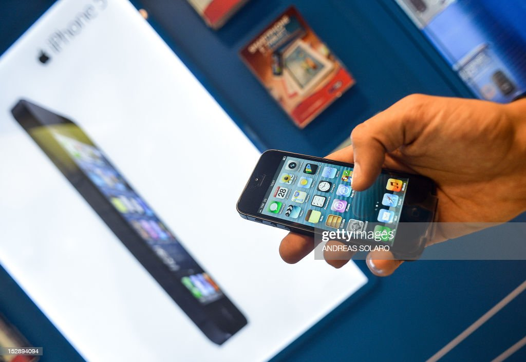 A customers holds the new Apple iPhone 5 smartphone in a telephone operator's shop in central Rome, on September 28, 2012. The new iPhone 5 broke records in its launch weekend with sales above five million, Apple said this week, but the figures were below some forecasts and pressured the company's share price.