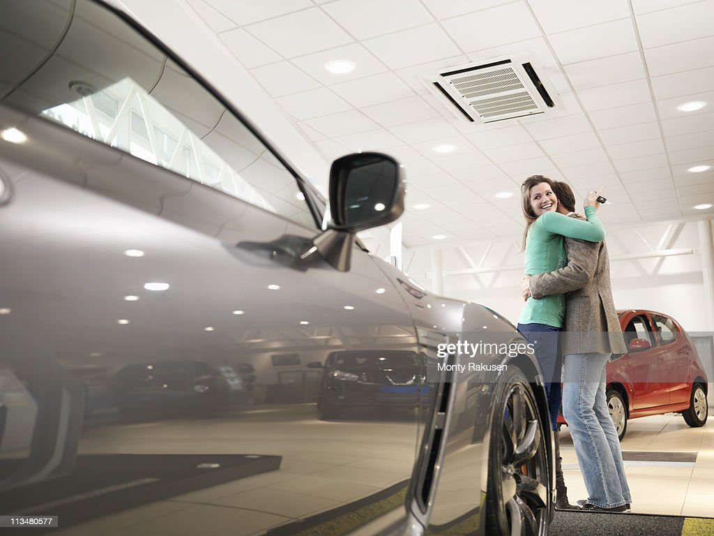 Customers hugging in car dealership.  Female customer looking at car and holding keys