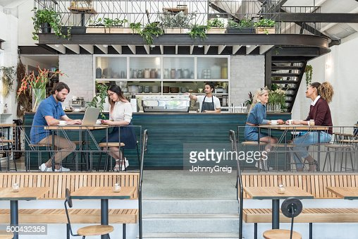 Customers in modern cafe with drinks and laptop