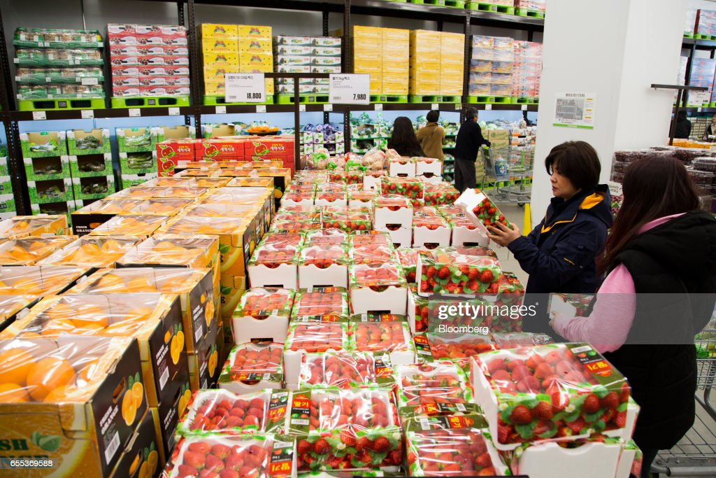 Customers inspect a box of strawberries at an E-Mart Inc. Traders store in the Starfield Hanam shopping complex, operated by Shinsegae Co., in Hanam, Gyeonggi, South Korea, on Wednesday, March 15, 2017. South Korea is scheduled to release consumer confidence figures on March 24. Photographer: SeongJoon Cho/Bloomberg via Getty Images