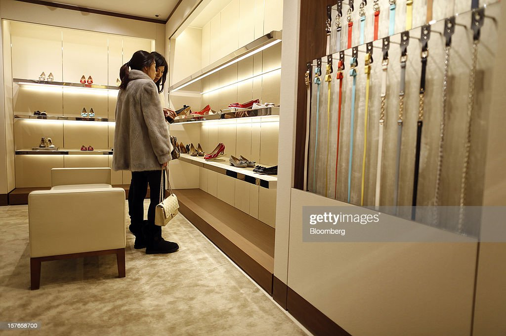 Customers inspect a display of women's high-heeled shoes inside Salvatore Ferragamo SpA's Sloane Street store in London, U.K., on Wednesday, Dec. 5, 2012. Demand for Ferragamo's shoes and other items is increasing even as China's economy slows and Europe's debt crisis weighs on consumer spending. Photographer: Simon Dawson/Bloomberg via Getty Images