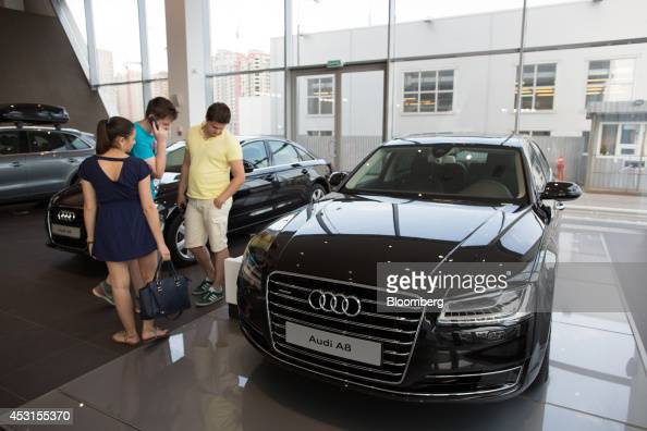 Customers inspect a new Audi A8 vehicle on display inside an Audi AG automobile showroom in Moscow Russia on Saturday Aug 2 2014 Prime Minister...