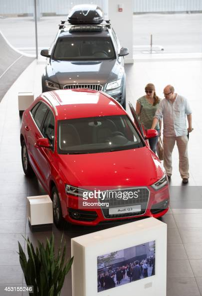 Customers inspect a red Audi Q3 automobile on display inside an Audi AG showroom in Moscow Russia on Saturday Aug 2 2014 Prime Minister Dmitry...