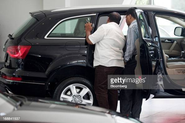 Customers inspect a Volkswagen AG Audi Q7 sportutility vehicle on display inside the Audi Delhi South dealership in New Delhi India on Wednesday May...