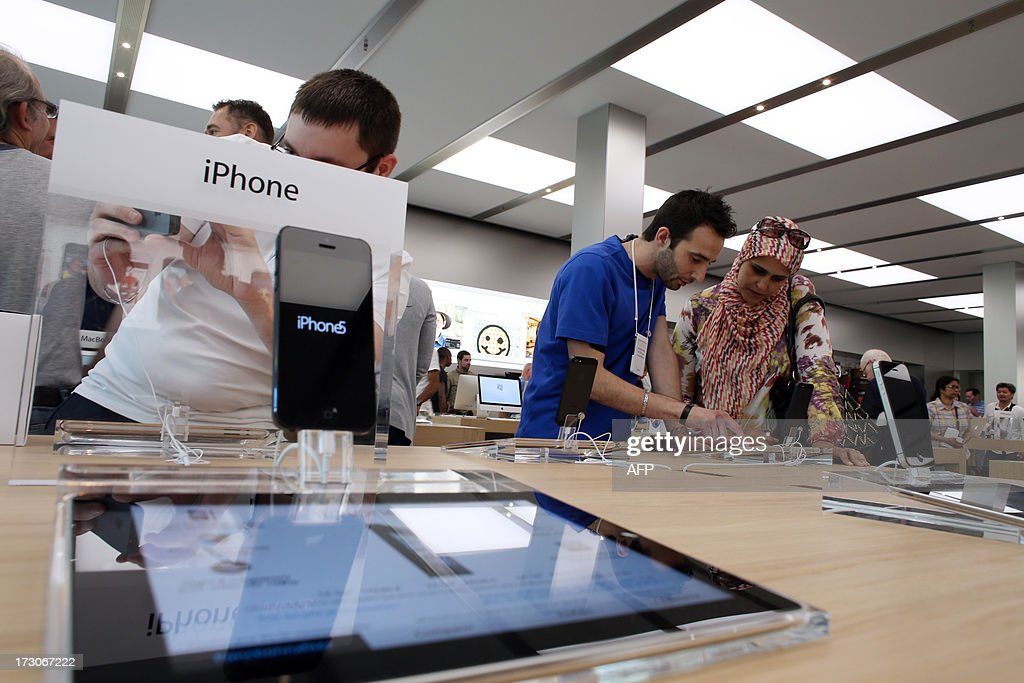 Customers inspect Apple's iPads and iPhone 5 smartphones in a new Apple store on July 6, 2013 in Rosny-sous-Bois, near Paris. AFP PHOTO / THOMAS SAMSON