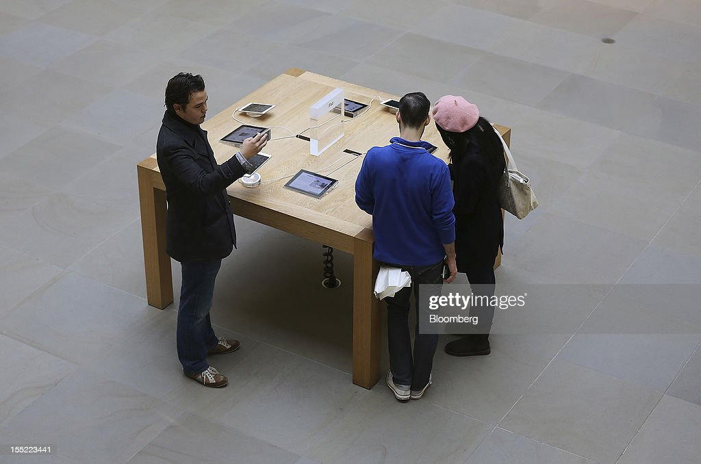 Customers inspect display models of Apple Inc. iPad minis at the company's Covent Garden store in London, U.K., on Friday, Nov. 2, 2012. Apple Inc.'s iPad mini tablet goes on sale in the U.K. today. Photographer: Simon Dawson/Bloomberg via Getty Images
