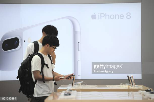 Customers inspect new iPhone 8 and plus models at a telecom shop in Omotesando Avenue in Tokyo Japan on September 22 2017 Apple sales its new iPhone...