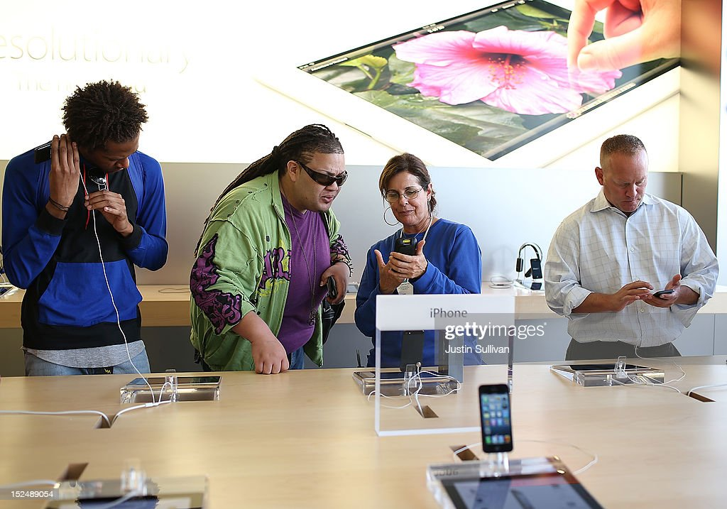Customers inspect the new iPhone 5 at an Apple Store on September 21, 2012 in San Francisco, California. Customers flocked to Apple Stores across the U.S. to purchase the hotly anticipated iPhone 5 which went on sale nationwide today.