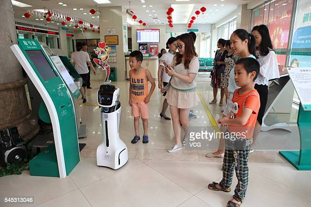 Customers interact with an intelligent robot at hall of Sichuan Neijiang Branch Agriculture Bank of China on July 7 2016 in Neijiang Sichuan Province...