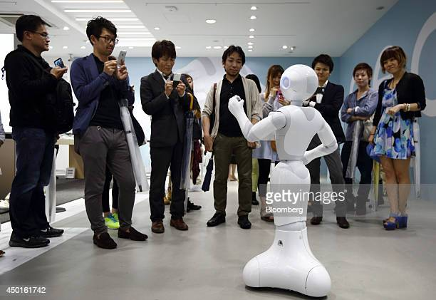 Customers interact with the humanoid robot Pepper developed by SoftBank Corp's Aldebaran Robotics SA unit at a SoftBank store in Tokyo Japan on...