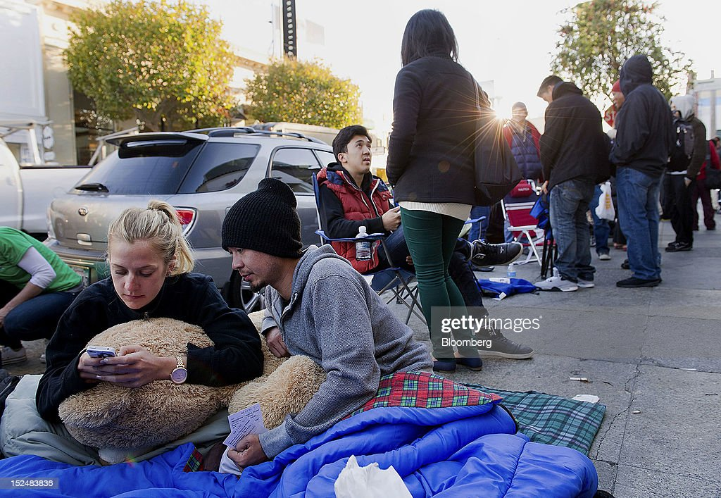 Customers Julianne Paulson, left, and Joe Borgue wait in line outside an Apple Inc. store to buy the new iPhone 5 in San Francisco, California, U.S., on Friday, Sept. 21, 2012. Apple Inc. is poised for a record iPhone 5 debut and may not be able to keep up with demand as customers lined up in Sydney, Tokyo, Paris and New York to pick up the latest model of its top-selling product. Photographer: David Paul Morris/Bloomberg via Getty Images