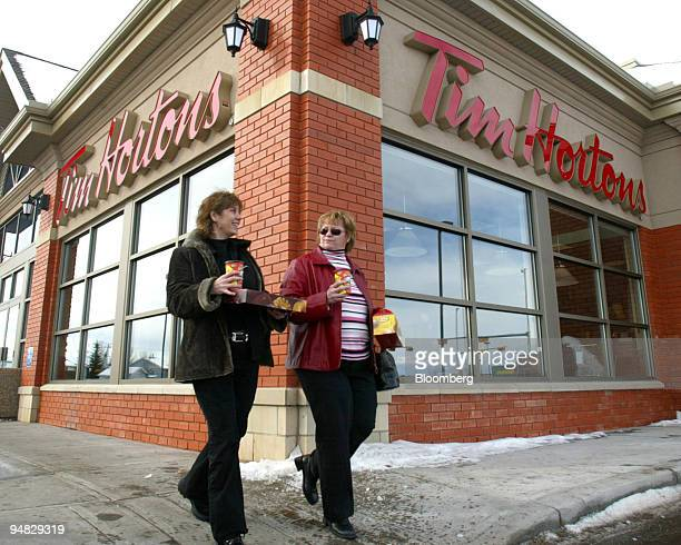 Customers Kim O'Brien left and Heather Arnfinson leave a Calgary Alberta Canada Tim Hortons store with coffee and donuts on Tuesday March 7 2006...