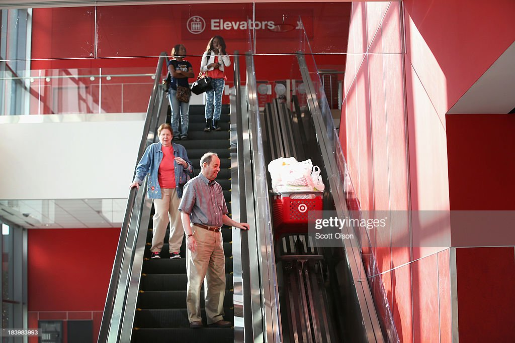 Customers leave a Target store with merchandise on October 10, 2013 in Chicago, Illinois. The store, which opened on October 8, was built on land where the notorious Cabrini-Green housing project once stood. The last of the Cabrini-Green high-rise homes were demolished two years ago. The housing project has been replaced with townhomes and retail shops, with some of the property being left vacant.