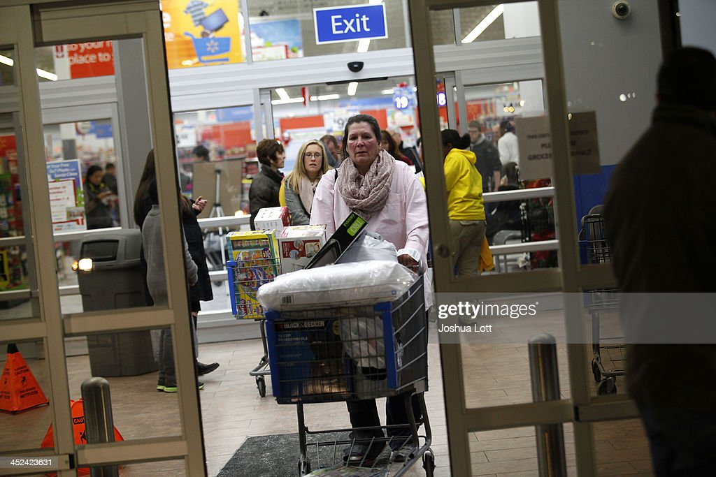 Customers leave Wal-Mart with their purchased items Thanksgiving day on November 28, 2013 in Troy, Michigan. Black Friday shopping began early this year with most major retailers opening their doors on Thanksgiving day as consumers took advantage of discounted prices to prepare for the holiday season.