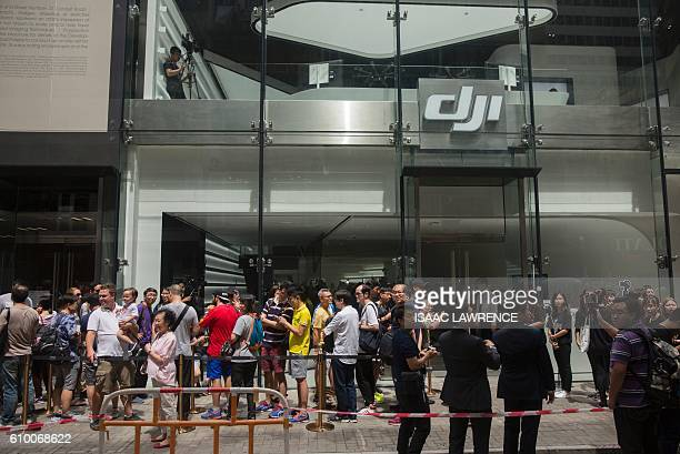 Customers line up as they wait to visit the new DJI flagship store in the Causeway Bay district of Hong Kong on September 24 2016 DJI is a Chinese...