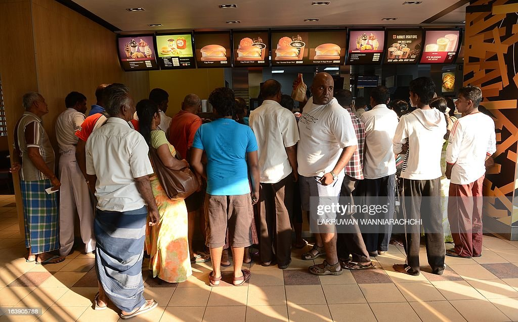 Customers line up at a McDonald's store as they give away 1,000 burgers free to mark national Breakfast Day in the capital Colombo on March 18, 2013. Six McDonald's stores took part in the promotion that was snapped up within a few minutes of opening, according to store officials.